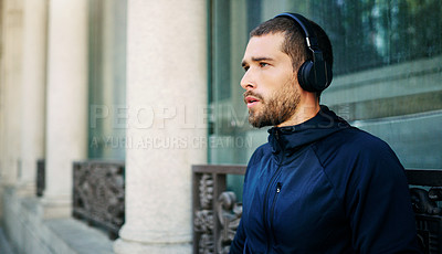 Buy stock photo Shot of a young man listening to music during his workout in the city