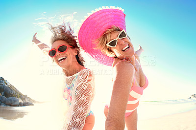 Buy stock photo Cropped portrait of two senior female friends taking a selfie together while enjoying a day at the beach