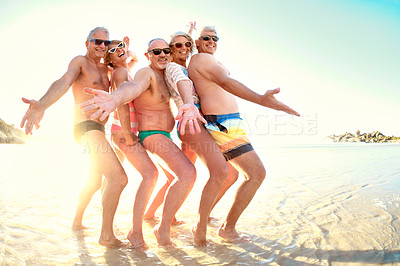 Buy stock photo Full length portrait of a group of senior friends being playful together while out at the beach