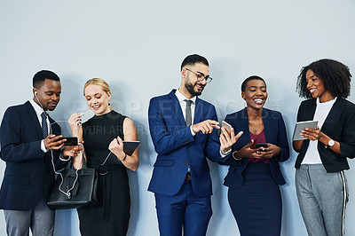 Buy stock photo Cropped shot of a diverse group of businesspeople standing and using technology while waiting for their interview in the studio