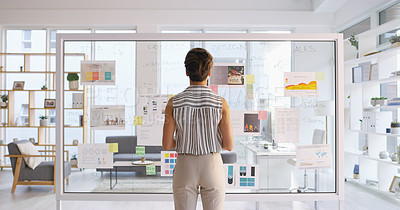 Buy stock photo Rearview shot of a young businesswoman writing down ideas on a glass wall in her office