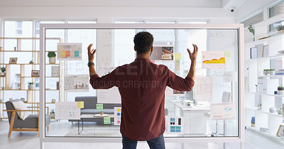 Buy stock photo Rearview shot of a young businessman looking frustrated while brainstorming ideas on a glass wall in his office