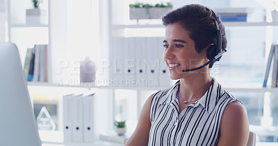 Buy stock photo Shot of an attractive young businesswoman wearing headsets and working on a computer in her office