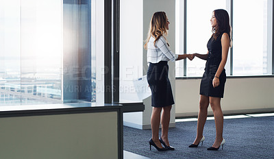 Buy stock photo Shot of two businesswoman shaking hands in a modern office