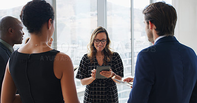 Buy stock photo Shot of a businesswoman using a digital tablet while talking to her colleagues