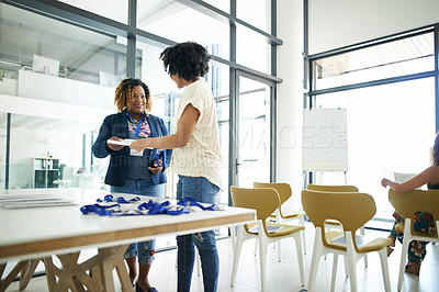 Buy stock photo Cropped shot of an attractive young businesswoman handing over a document to an attendee at a conference