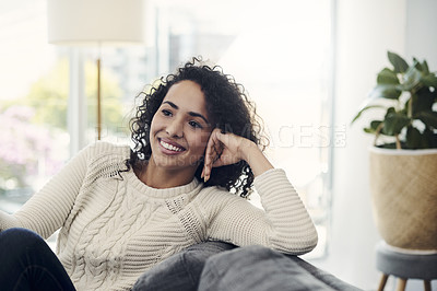 Buy stock photo Cropped shot of an attractive young woman looking contemplative relaxing on her couch at home