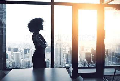 Buy stock photo Cropped shot of an attractive young businesswoman standing with her arms crossed and looking out from her high-rise office
