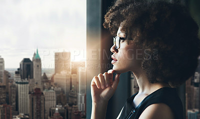Buy stock photo Cropped shot of an attractive young businesswoman standing with her hand on her chin and looking contemplative in her office