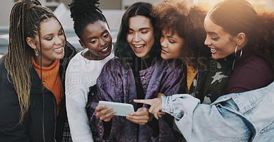 Buy stock photo Shot of a group of young women using a smartphone together in the city
