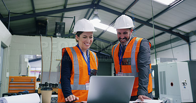 Buy stock photo Shot of two engineers using a laptop together in an industrial place of work