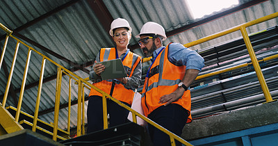 Buy stock photo Shot of two engineers using a digital tablet together in an industrial place of work