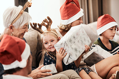 Buy stock photo Cropped shot of a cheerful little girl holding a present while being seated with her family during Christmas time