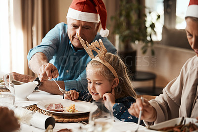 Buy stock photo Cropped shot of a cheerful elderly man dishing food into his granddaughter's plate at lunch during Christmas time
