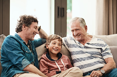 Buy stock photo Cropped shot of a cheerful little boy seated on a sofa with his father and grandfather during Christmas time