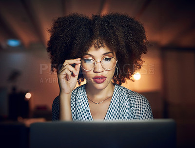 Buy stock photo Shot of a beautiful young businesswoman using a laptop while working late in her office