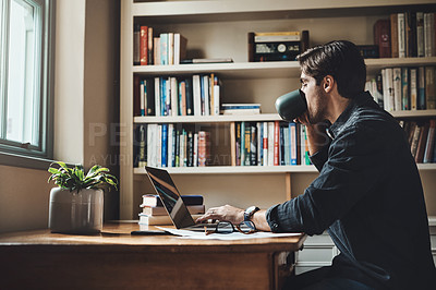 Buy stock photo Shot of a handsome young businessman drinking coffee while working on a laptop in his home office