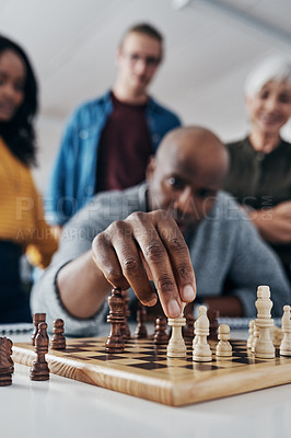 Buy stock photo Shot of a mature businessman playing chess in his office with his colleagues rooting and watching in the background