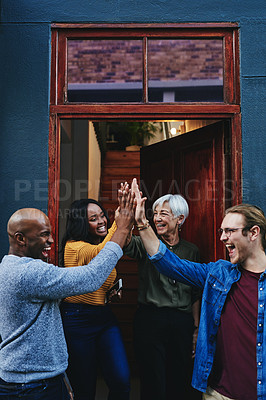 Buy stock photo Shot of a group of businesspeople joining together for a high five while standing outside their office building