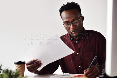 Buy stock photo Cropped shot of a handsome young businessman sitting and making notes while working with documents in the office