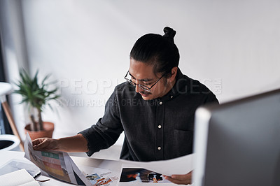 Buy stock photo Cropped shot of a handsome young businessman looking at paperwork and sitting alone at his desk in the office