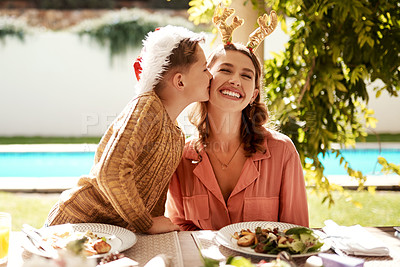 Buy stock photo Cropped shot of a girl girl and her mother enjoying Christmas lunch together
