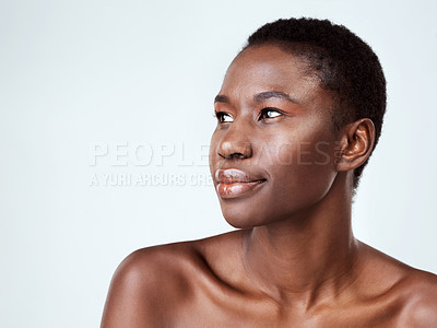 Buy stock photo Studio shot of a beautiful young woman looking thoughtful against a grey background