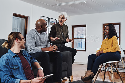 Buy stock photo Shot of a group of businesspeople having a meeting and discussing ideas in their office at work