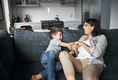 Buy stock photo Shot of a little boy tickling his mother at home