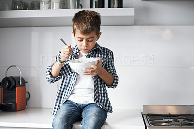 Buy stock photo Shot of an adorable little boy eating from a bowl at home