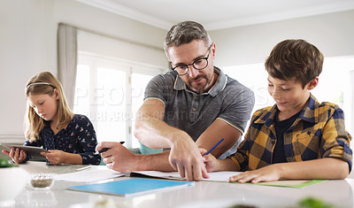 Buy stock photo Cropped shot of a handsome mature man helping his two kids with their schoolwork at home