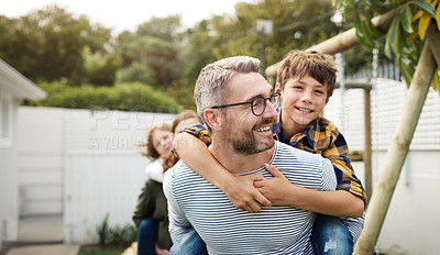 Buy stock photo Shot of a handsome mature man piggybacking his son through the garden with his wife and daughter in the background