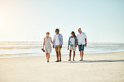 Buy stock photo Shot of a group of senior adults going for a leisurely walk on the beach