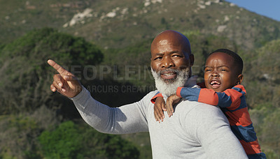 Buy stock photo Cropped shot of a senior man pointing at something while giving his cute grandson a piggyback on the beach