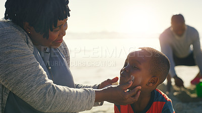 Buy stock photo Cropped shot of an attractive senior woman putting sunblock on her cute grandson as they play on the beach