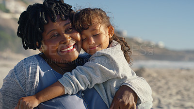 Buy stock photo Cropped shot of an attractive senior woman hugging her granddaughter as they sit on the beach in the afternoon