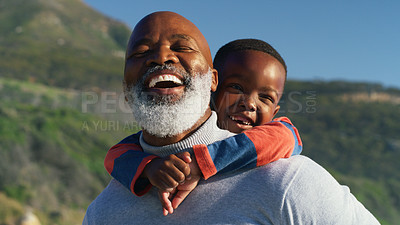 Buy stock photo Cropped shot of a happy senior man giving his cute grandson a piggyback ride on the beach