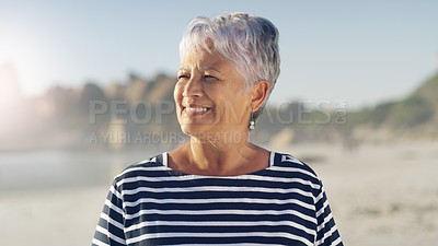 Buy stock photo Cropped shot of an attractive senior woman standing alone and enjoying the fresh air at the beach