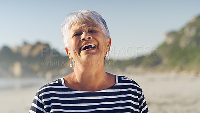Buy stock photo Cropped shot of an attractive senior woman standing alone  and smiling while enjoying a day out on the beach