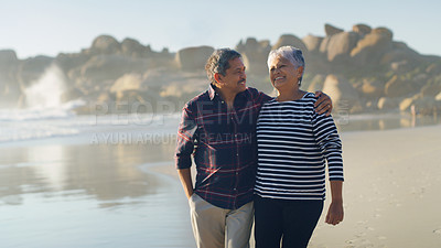Buy stock photo Cropped shot of a happy senior couple walking along the beach and holding each other affectionately