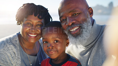 Buy stock photo Cropped portrait of a happy senior couple taking a selfie with their cute grandson on the beach