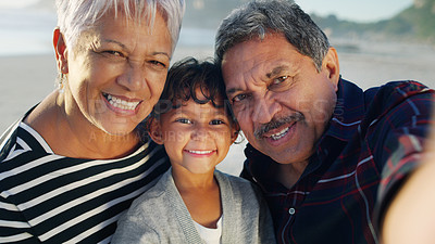 Buy stock photo Cropped portrait of a happy senior couple taking a selfie with their cute granddaughter on the beach