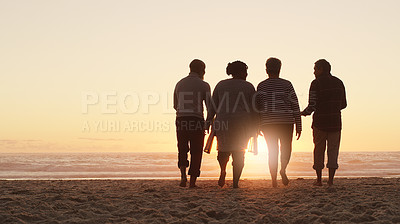 Buy stock photo Full length shot of a group of friends enjoying a day out and walking along the beach together