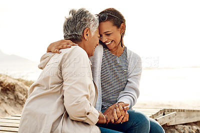 Buy stock photo Shot of a senior woman and her adult daughter spending the day together at the beach