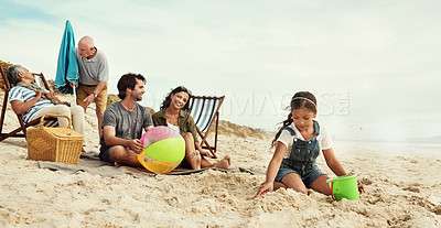 Buy stock photo Shot of a little girl playing in the sand at the beach with her parents and grandparents in the background