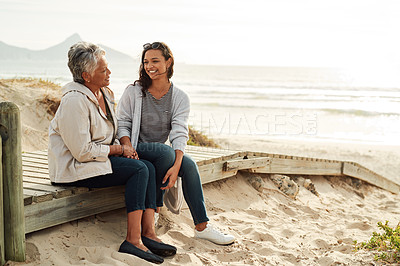 Buy stock photo Full length shot of a senior woman and her adult daughter spending the day together at the beach
