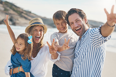 Buy stock photo Cropped portrait of a happy couple carrying their two children and making peace sign gestures on the beach