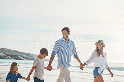 Buy stock photo Cropped shot of a happy couple holding hands with their two young children and walking along the beach