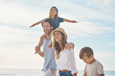 Buy stock photo Cropped shot of a happy couple bonding with their two children during a day out on the beach together