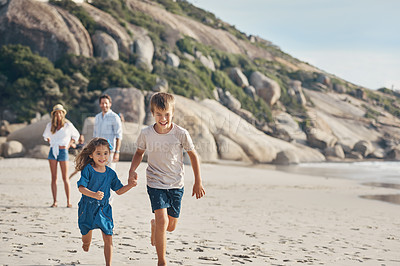 Buy stock photo Cropped shot of two happy siblings holding hands and running along the beach together while their parents watch